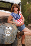 Cowgirl Leaning on Antique Truck. A cowgirl wearing a stars and strips T-shirt in Santa Fe New Mexico leans against a rusty antique truck stock photo