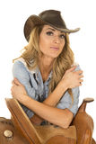 Cowgirl leaning on saddle with arms crossed Royalty Free Stock Photography