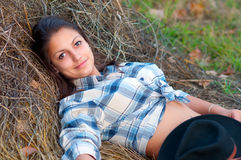 Cowgirl lies on the pile of hay Stock Photography