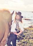 Cowgirl lindo con su caballo en el golfo. Imagen de archivo