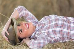 Cowgirl lying hay Stock Image