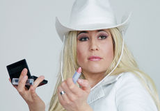 Cowgirl With Makeup. Head and shoulders portrait of a beautiful young blond woman in a white outfit and white cowgirl hat, with a lipstick in one hand, and an royalty free stock image