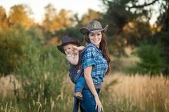 Cowgirl Mother Carrying Her Small Daughter In A Baby Sling Stock Images