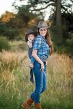 Cowgirl Mother Carrying Her Small Daughter In A Baby Sling Stock Photos