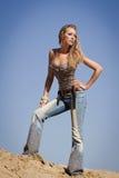 Cowgirl nas calças de brim em um fundo arenoso Foto de Stock