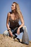 Cowgirl nas calças de brim em um fundo arenoso Imagem de Stock