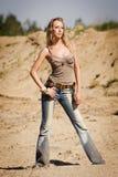 Cowgirl nas calças de brim em um fundo arenoso Fotografia de Stock Royalty Free