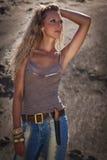 Cowgirl nas calças de brim em um fundo arenoso Imagem de Stock Royalty Free