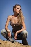 Cowgirl nas calças de brim em um fundo arenoso Foto de Stock Royalty Free