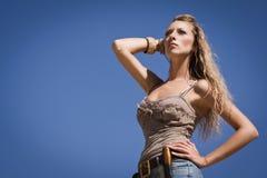 Cowgirl nas calças de brim em um fundo do céu azul Fotos de Stock Royalty Free