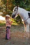 Cowgirl novo com pônei. Fotografia de Stock