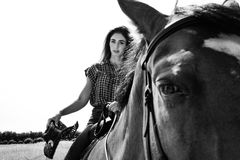 Cowgirl patrzeje kamerę podczas gdy jeździecki koń z westernu kapeluszem i comberem fotografia royalty free