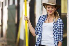 Cowgirl pitch fork. Pretty cowgirl holding a pitch fork inside stable Royalty Free Stock Photo