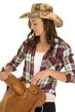 Cowgirl plaid shirt hat hold saddle close stock photos
