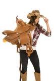 Cowgirl plaid shirt hat hold saddle on shoulder Royalty Free Stock Photo