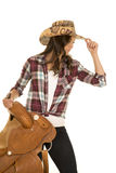 Cowgirl plaid shirt hat hold saddle touch hat royalty free stock images