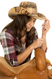 Cowgirl in plaid shirt and hat lean on saddle look down Royalty Free Stock Photos