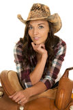 Cowgirl in plaid shirt and hat lean on saddle looking Royalty Free Stock Photography