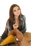 Cowgirl in plaid shirt lead lean on saddle Royalty Free Stock Photo