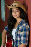 Cowgirl playing guitar by the barn Royalty Free Stock Images