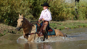 Cowgirl in Pond. Cowgirl crossing pond on palomino horse royalty free stock photo