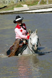 Cowgirl in Pond. Cowgirl crossing pond on gray horse royalty free stock photography
