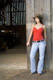 Cowgirl in porta del granaio Fotografia Stock