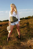 Cowgirl portraits. Young blond cowgirl stands in a field at sunset Royalty Free Stock Photography