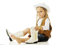 Cowgirl Putting on Boots. An adorable little cowgirl putting on her boots.  On a white background Stock Photography