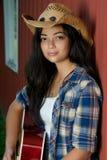 Cowgirl que toca la guitarra por el granero Imágenes de archivo libres de regalías