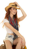 Cowgirl with red hair sit on saddle touch hat Stock Photography