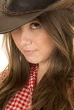 Cowgirl red white shirt close look with one eye under hat Stock Image