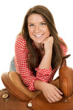 Cowgirl red white shirt saddle lean chin smile Royalty Free Stock Photo