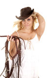 Cowgirl reins smiling. A cowgirl is holding her hat with one hand and a bridle with the other and smiling Royalty Free Stock Photo