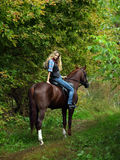 Cowgirl ride back horse in a evening woods Royalty Free Stock Images