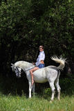 Cowgirl ride back horse in a evening woods Royalty Free Stock Image
