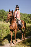 Cowgirl riding a bay horse Royalty Free Stock Photo