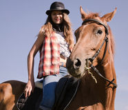 Cowgirl riding a bay horse Stock Image