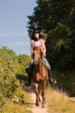 Cowgirl riding a bay horse Stock Photo