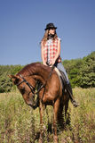 Cowgirl riding a bay horse Stock Photography