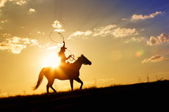 Cowgirl roping on horizon Stock Images