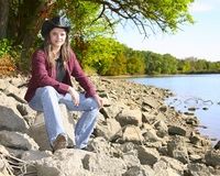 Cowgirl sat by river Royalty Free Stock Images