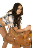Cowgirl short denim shorts lean over on saddle Stock Images