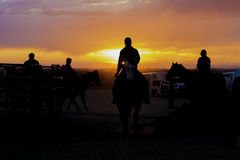 Cowgirl silhouettes in front of a colorful sunset Stock Images