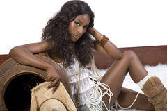 Cowgirl sitting. Gorgeous african cowgirl is sitting on the fur stock photography