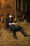 Cowgirl sitting on hay in the stable Royalty Free Stock Image