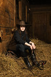 Cowgirl sitting on hay in the stable Royalty Free Stock Photos