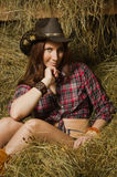 Cowgirl sitting on hay in the stable Stock Photos