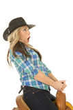 Cowgirl sitting on a saddle lean back mouth open Royalty Free Stock Image