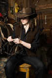 Cowgirl in the stables. Young cowgirl in the stables at the ranch Royalty Free Stock Photography